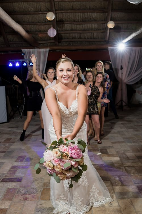 Bride throwing bouquet of flowers