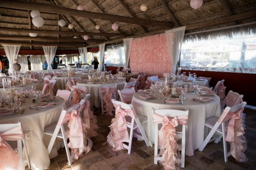 reception in tiki hut with pink ribbons on chairs